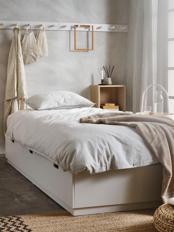NORDLI säng med förvaring bäddad med BERGPALM påslakanset i grått och TRATVIVA överkast i beige.