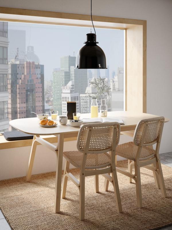 Reggelihez terített VOXLÖV étkezőasztal két, világos színű bambuszból készült székkel, melyek egy nagy ablakra néznek, melyből felhőkarcolókra látni.