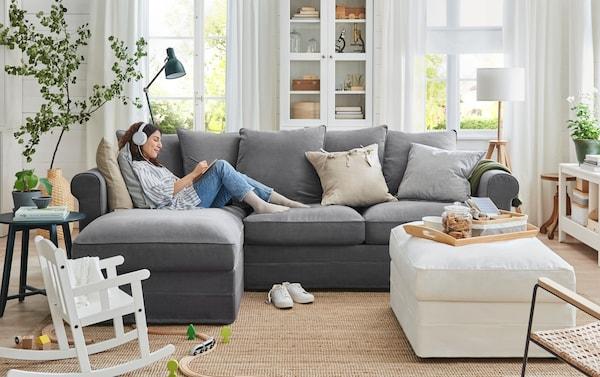 Egy világos nappaliban kanapén fekvő nő zenét hallgat.
