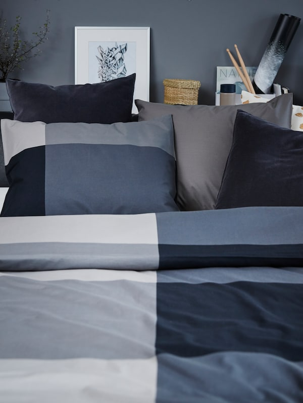 A black leather sofa-bed made up with black/grey bedding and cushions in grey, white/gold and dark cotton.