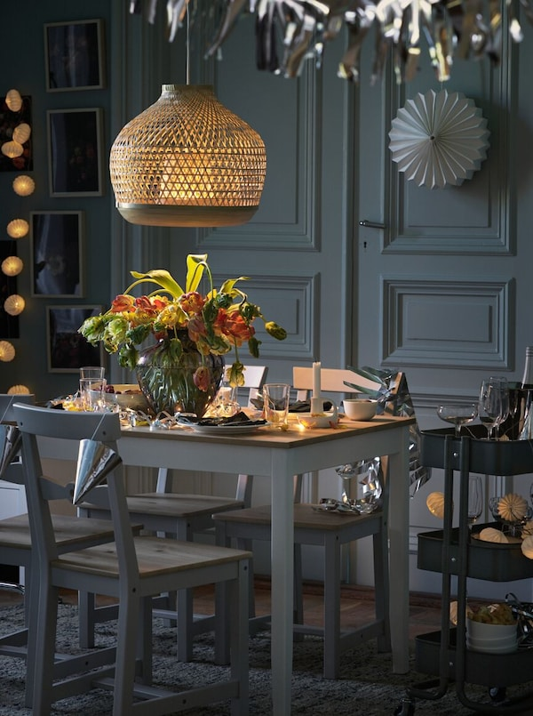 A LERHAMN table, set with tableware and flowers in a vase, and GAMLEBY chairs stand under a MISTERHULT pendant lamp.