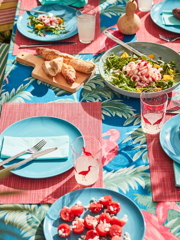 A sunny, summery table set with turquoise plates, light red place mats and a multi-colored tablecloth with flamingos.