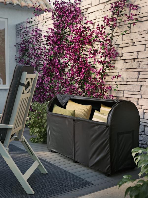 Eine TOSTERÖ Auflagenbox vor einer Steinwand mit Weinranken, u. a. mit einem Ruhesessel und grünen Kissen.