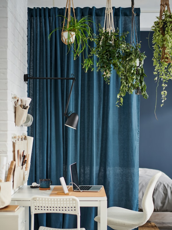 A white table with one white and one beige chair plus a black wall lamp above, beside blue DYTÅG curtains and hanging plants.