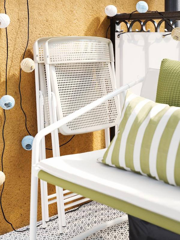 Dva bela/bež zložena stola slonita ob rumeni steni poleg majhne bele zunanje zofe z dvema zelenima blazinama.