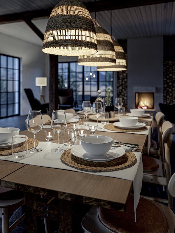 Set per la zona pranzo in legno con piatti e ciotole bianchi, posate, tovagliette all'americana intrecciate e portacandeline.
