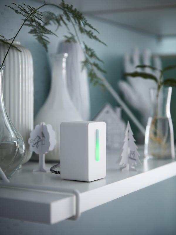 En hvid luftkvalitetssensor, glasvaser med stiklinger og et sæt med skabeloner af karton til en by med 10 dele.