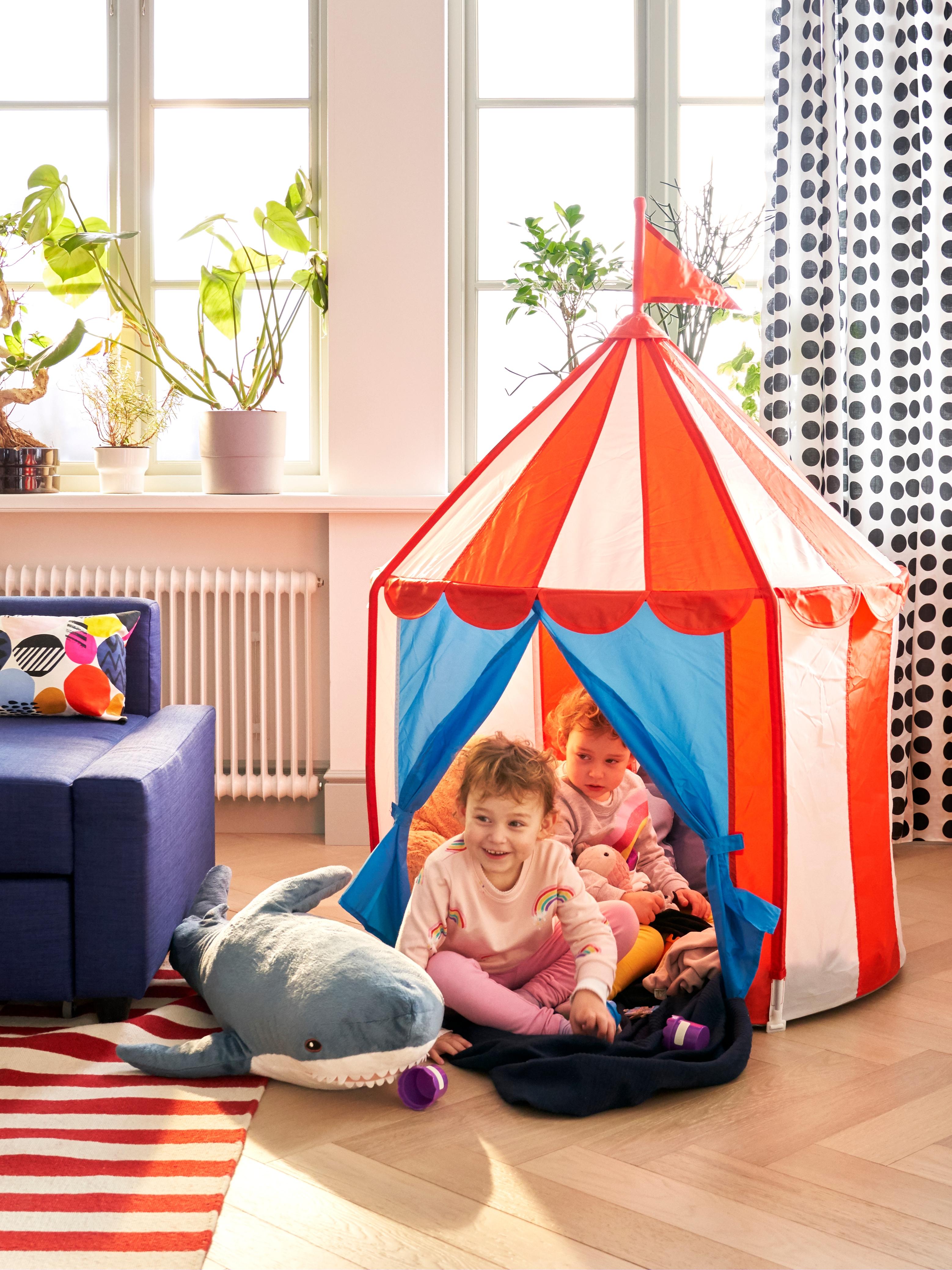 サーカスのテントのような形をしたCIRKUSTÄLT/スィルクステルト 子ども用テント。窓のある部屋に置かれており、テントの中では2人の小さな子どもが遊んでいます