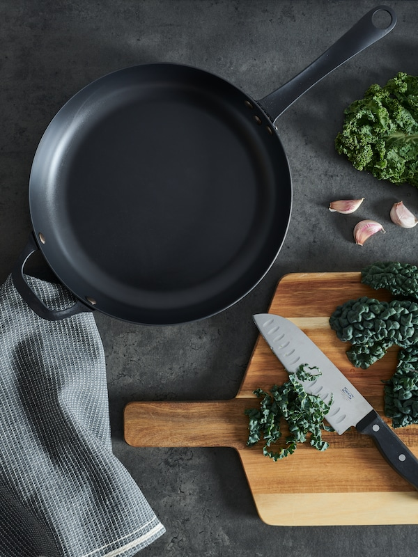 A grey worktop with an empty VARDAGEN frying pan sided by cavolo nero kale and a VARDAGEN knife on a SMÅÄTA chopping board.