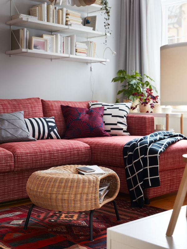 Ein GAMLEHULT Hocker mit Aufbewahrung auf einem rot gemusterten Teppich, u. a. mit einem roten Sofa, weissen Wandregalen und einem karierten Plaid.