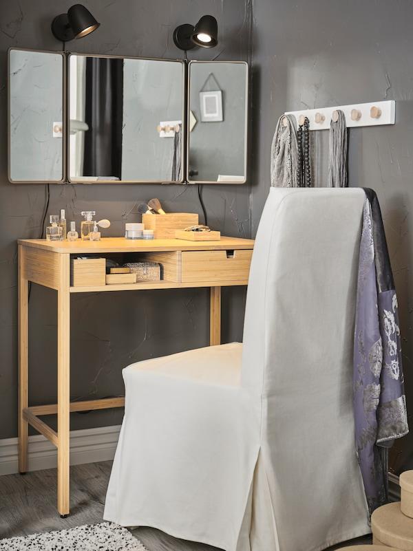 Makeuphjørne med et NORDISKA sminkebord og en HENRIKSDAL stol under et vægspejl og 2 væglamper.