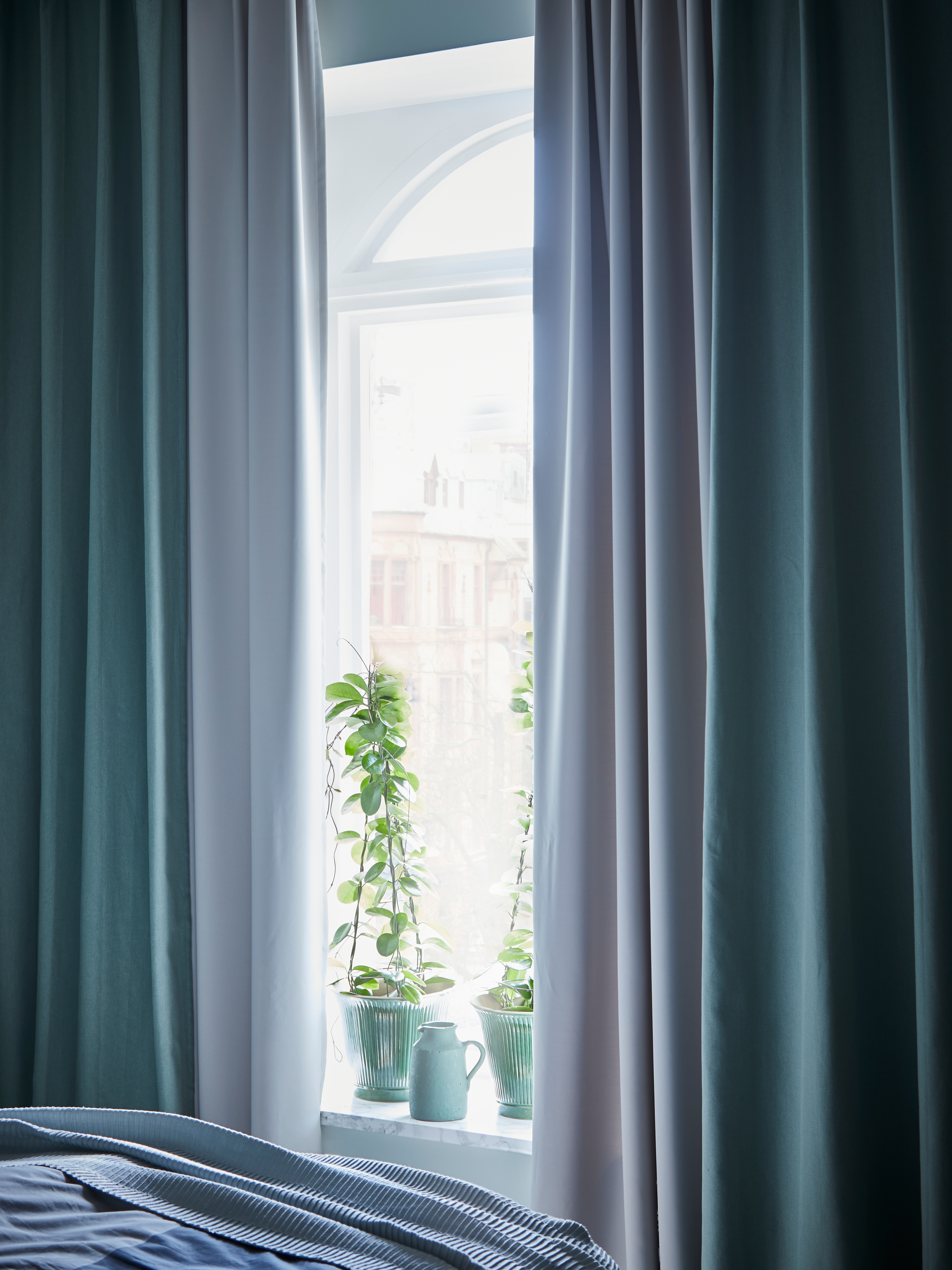 A bedroom window with MAJGUL room darkening curtains in light grey under blue curtains open to show plants in the windowsill.