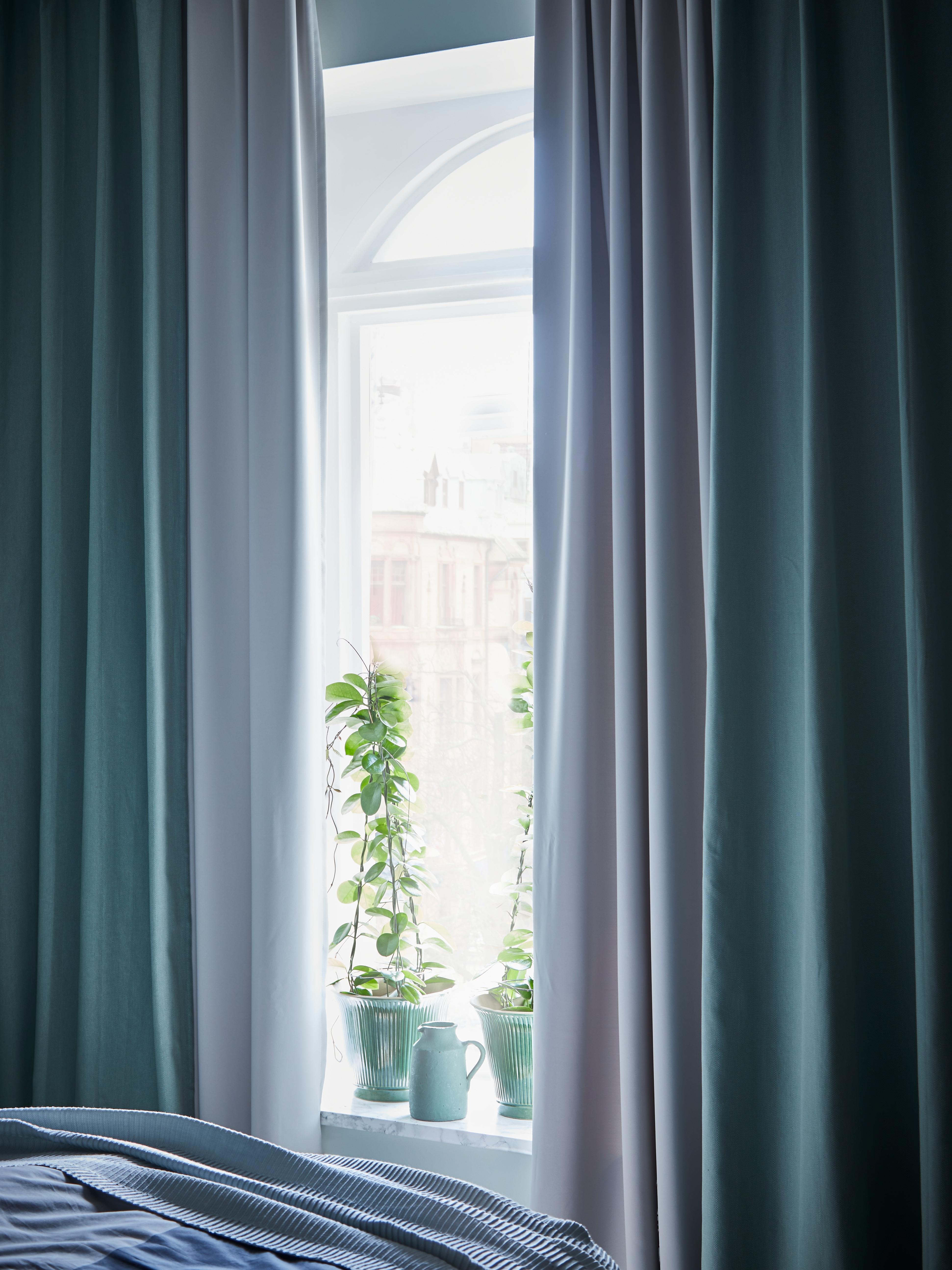 Camera da letto con tende semioscuranti MAJGUL grigio chiaro sotto tende blu e piante sul davanzale della finestra.