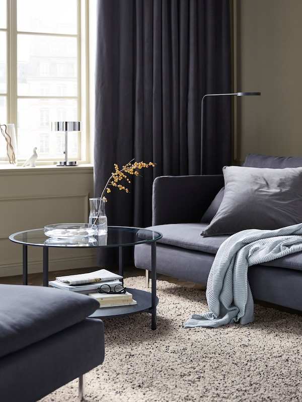 A living room with a gray sofa and gray cushions, a gray, white and black speckled rug and a coffee table and lamp.