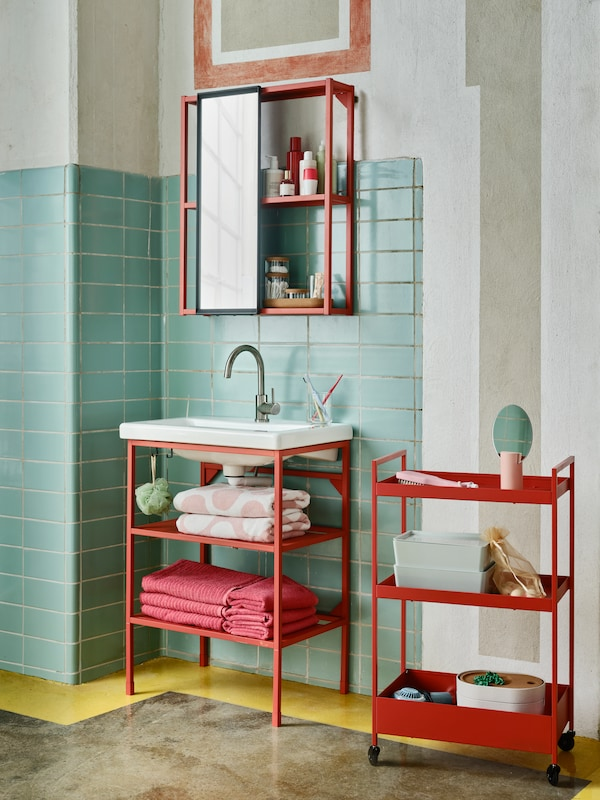 A bathroom with a red-orange, wall-mounted ENHET overhead storage module, a red-orange washbasin module, and a trolley.
