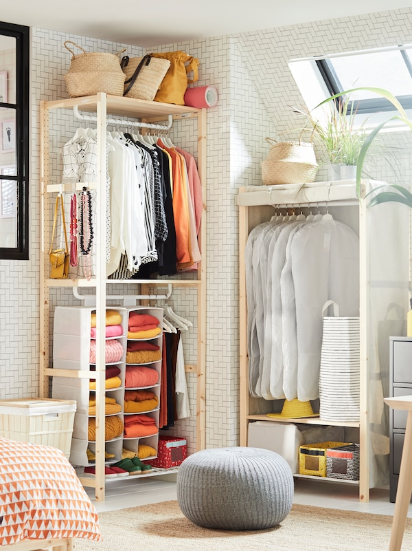 A corner of a bedroom with a lot of clothes hanging on rails and folded on hanging storage in two IVAR shelving units.