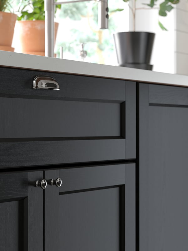 A close-up of kitchen cabinets with traditional LERHYTTAN doors in black stain fitted with cup handles and knobs.