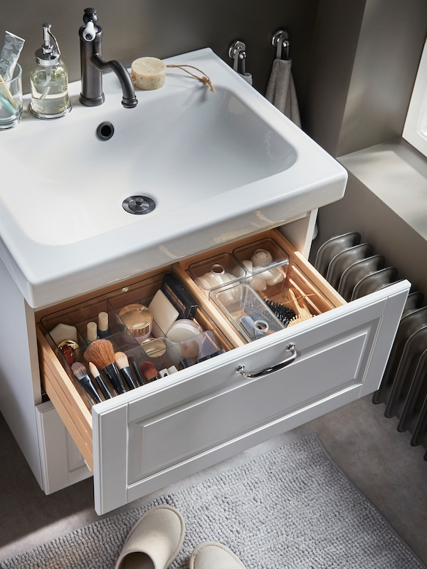 Makeup, hair and beauty tools are nicely organised in smoke-coloured see-through boxes that are in a wash-stand drawer.
