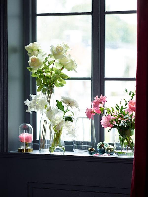A window sill full of beautiful flower arrangements in BERÄKNA vases.