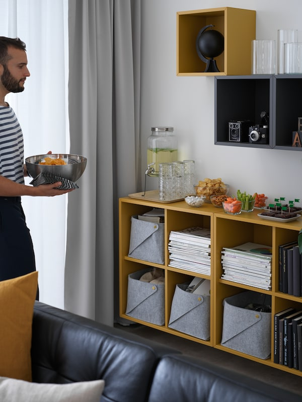 A bearded man prepares for guests by arranging party snacks on top of EKET storage cabinets in a living room.
