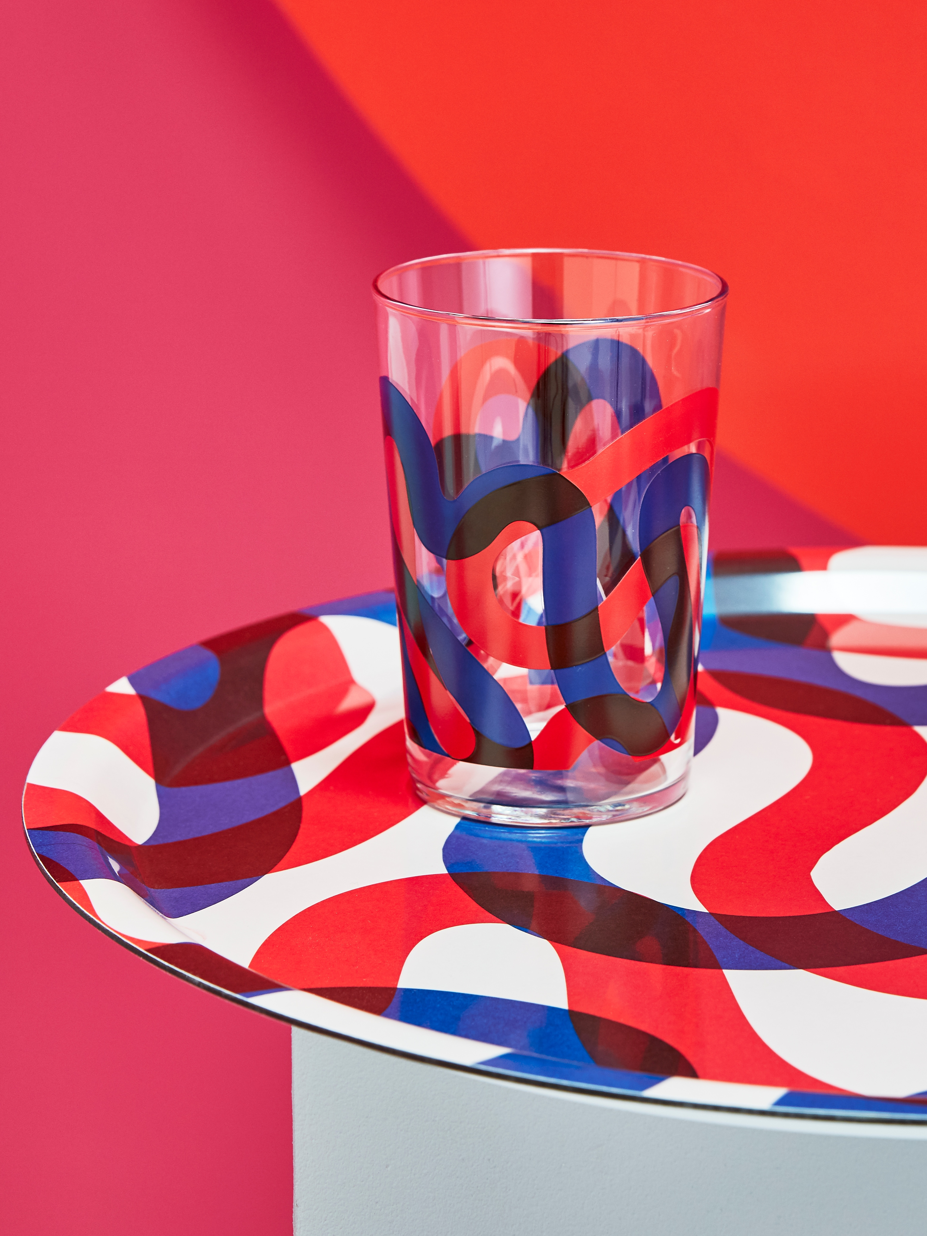 A close-up of a matching glass on a round, melamine FRAMKALLA patterned tray in white with big, red and blue squiggles.