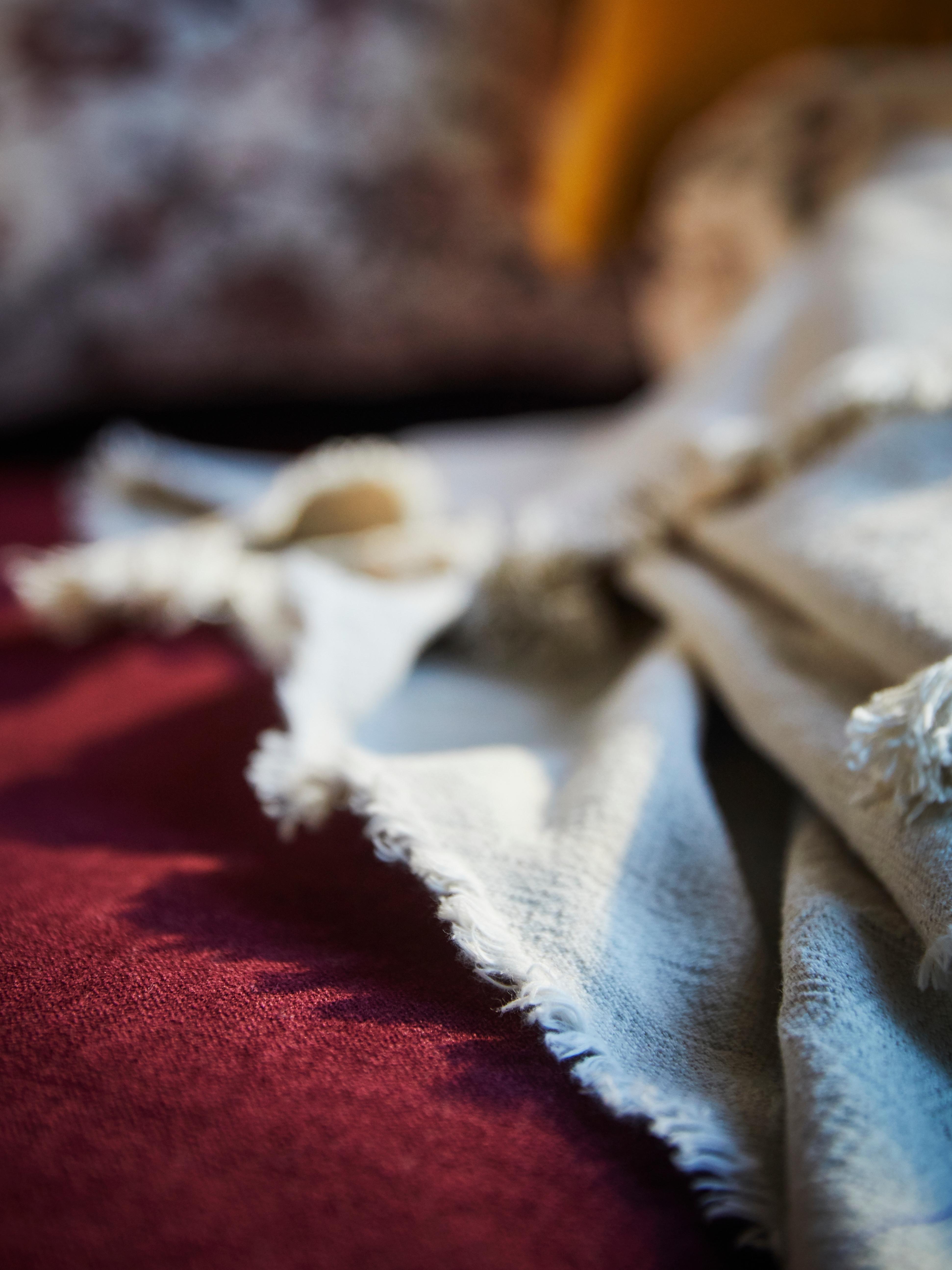 Un divano rosso in velluto e un plaid JOFRID in cotone e lino in tonalità naturale, illuminati di lato.