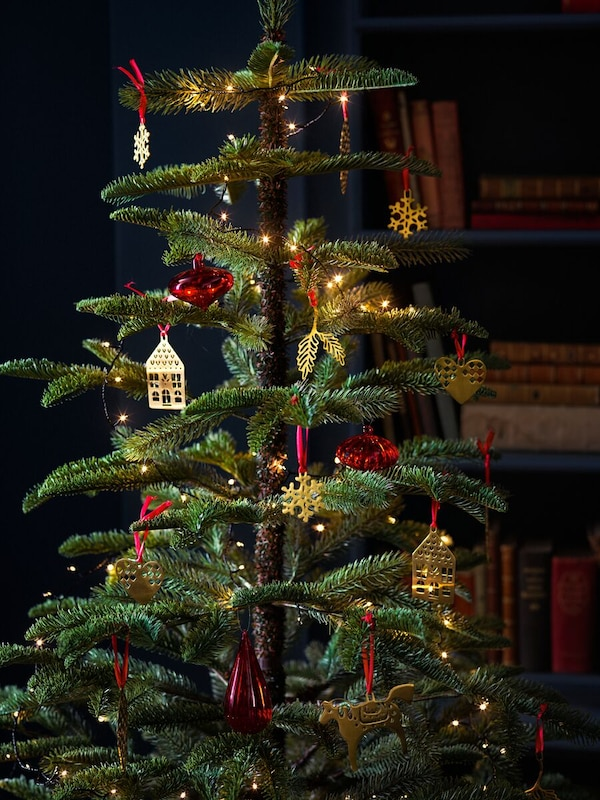 A seasonal tree adorned with many hanging decorations and lights in front of a bookcase with lots of books.