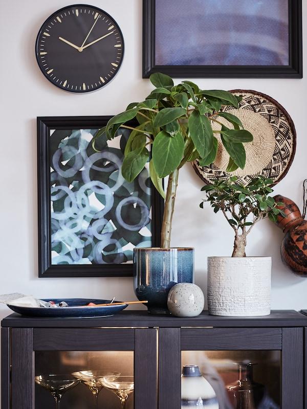 Secção de estante BILLY em branco com livros e plantas artificiais FEJKA em vários vasos.
