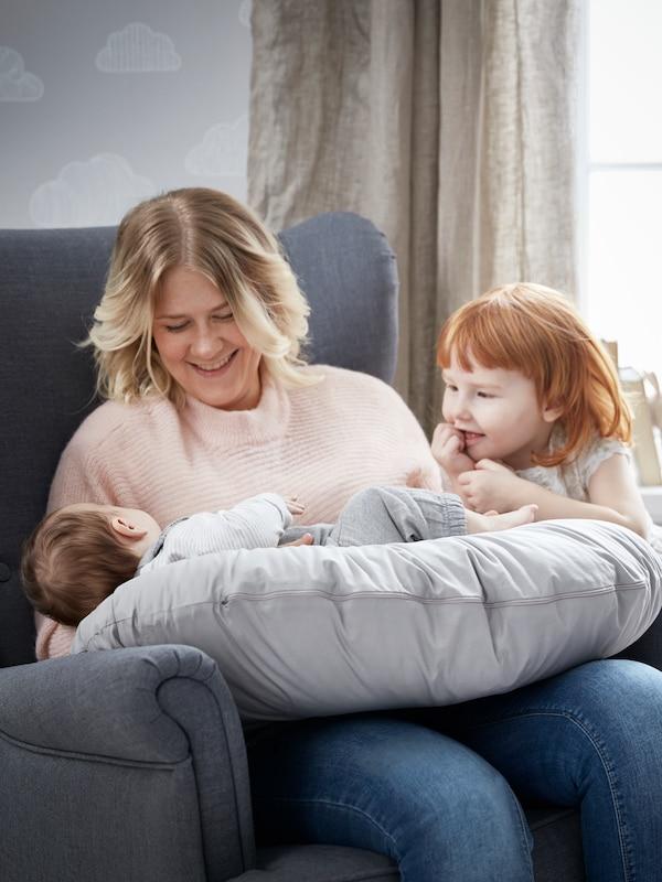 Una madre sentada en un sillón con su bebé encima sobre una almohada de lactancia LEN. Junto a ella hay una niña pequeña sonriendo.