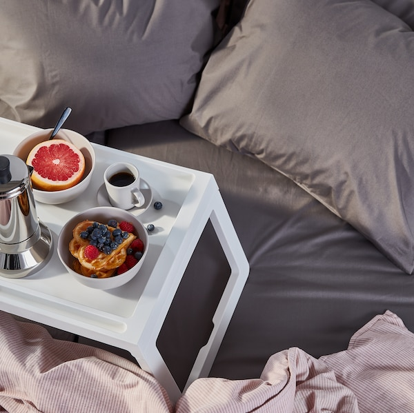 Coffee, waffle and grapefruit breakfast served on a KLIPSK bed tray, placed on a grey ULLVIDE fitted sheet on an unmade bed.