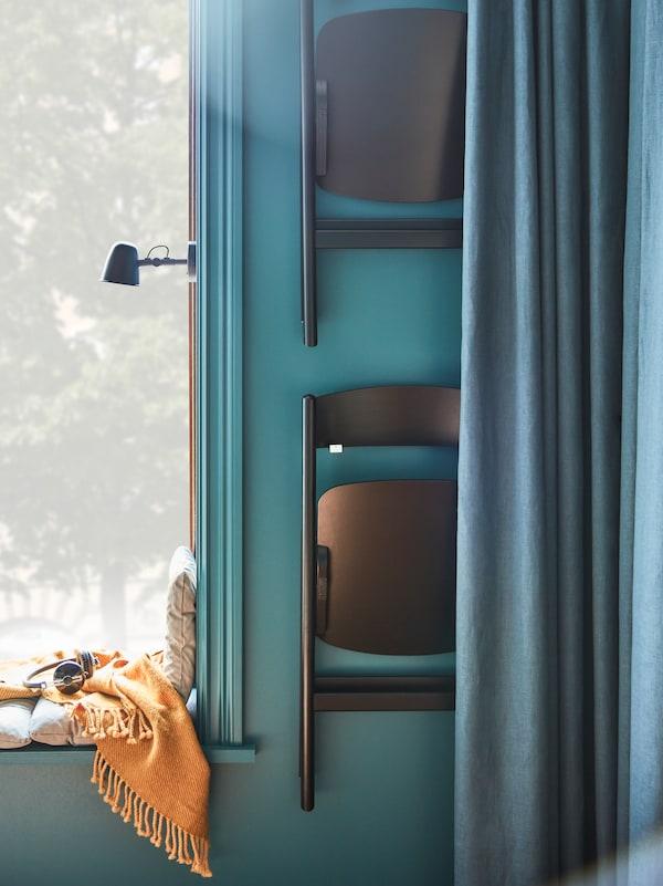 Dvě černé židle RÅVAROR zavěšené na stěně v rohu vedle okna, částečně zakryté modrým závěsem DYTÅG.