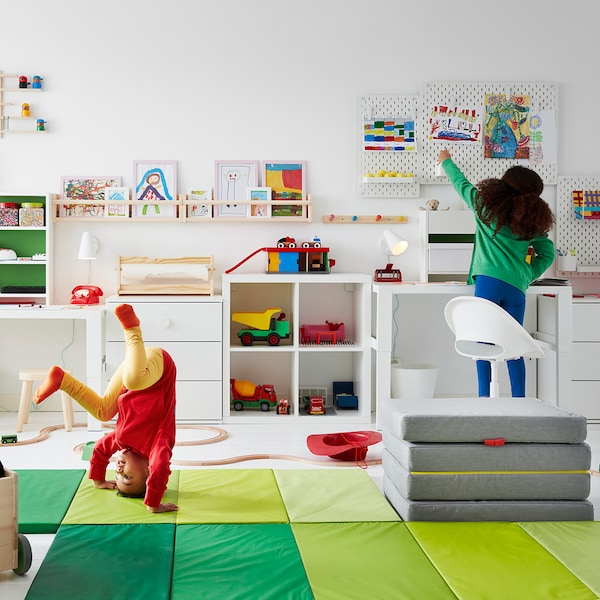 A kid does a headstand on a green PLUFSIG gym mat in a playroom, while another child reaches for a cubby on a pegboard.