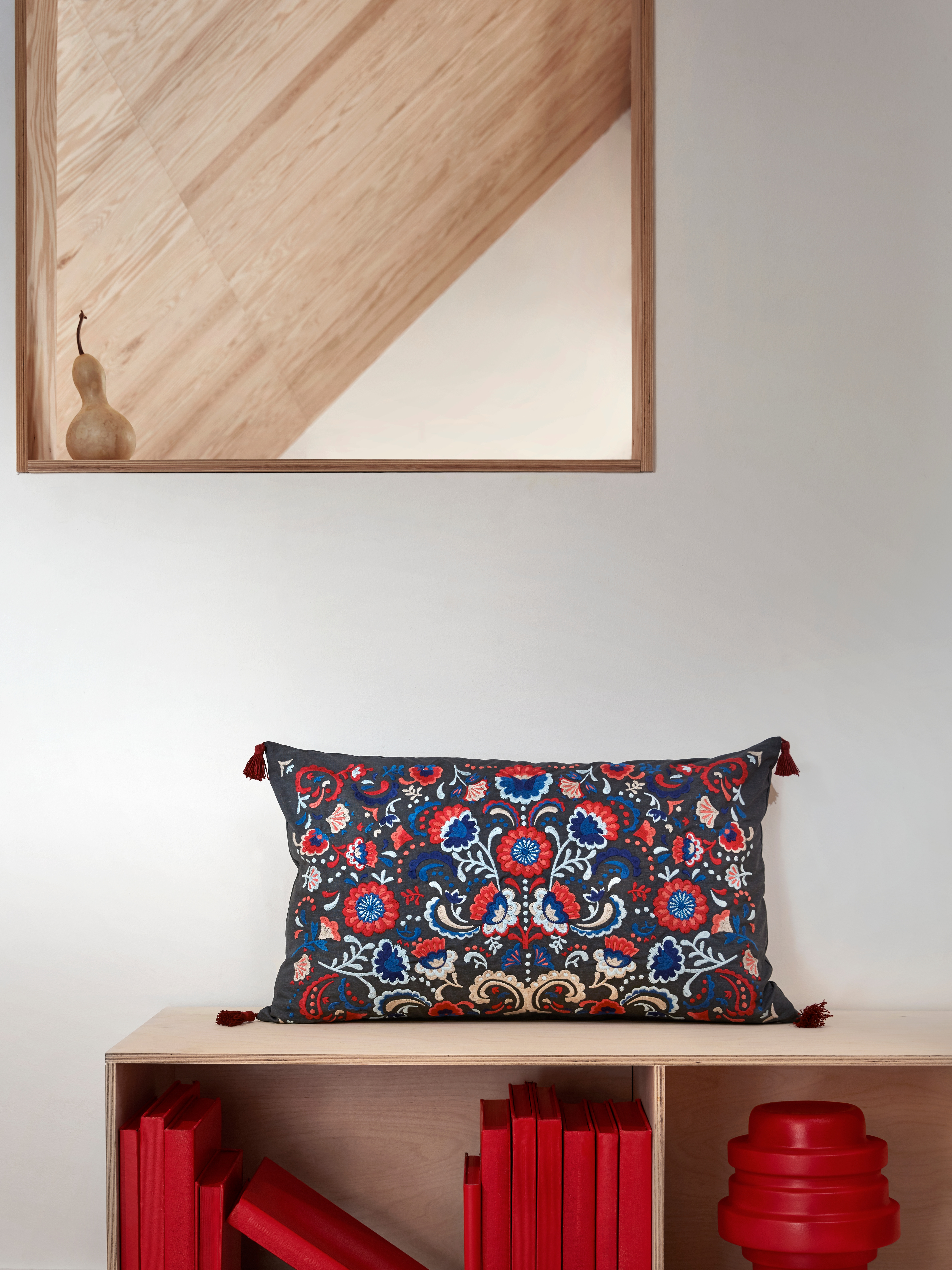 Dark rectangular SKOGSKORN cushion with multi-colored paisley embroidery and red tassels; placed on a wooden hallway bench.