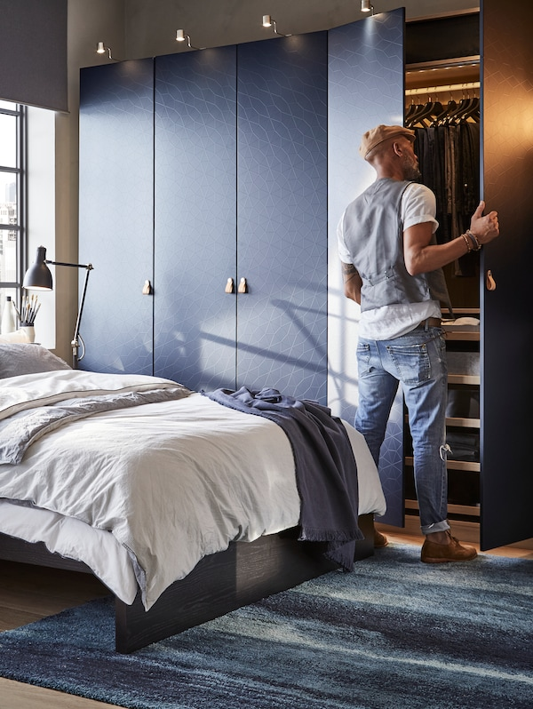 A man opens a door of a large black-blue PAX wardrobe beside a MALM bed. It contains hanging clothes and shelves.