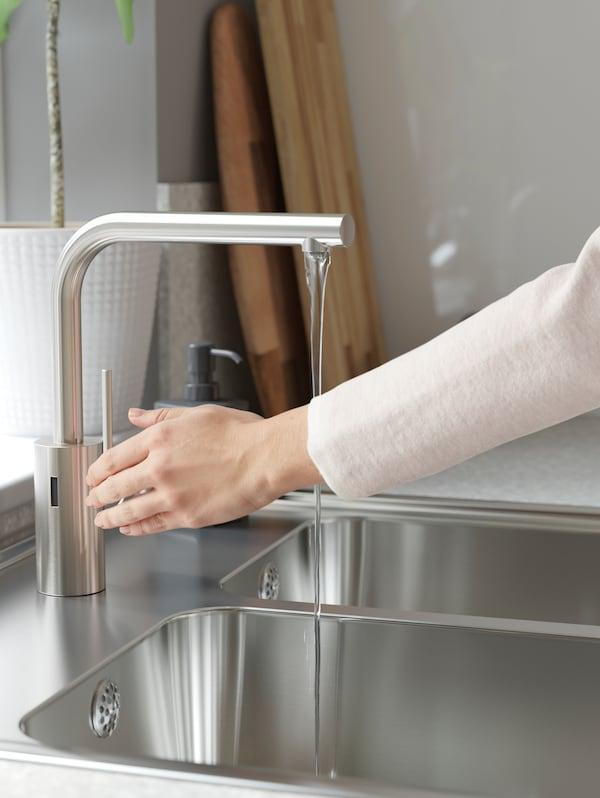 Prikaz osobe s bijelom majicom kako aktivira IKEA TÄMNAREN miješalicu za vodu od nehrđajućeg čelika sa senzorom pokreta i pušta vodu.