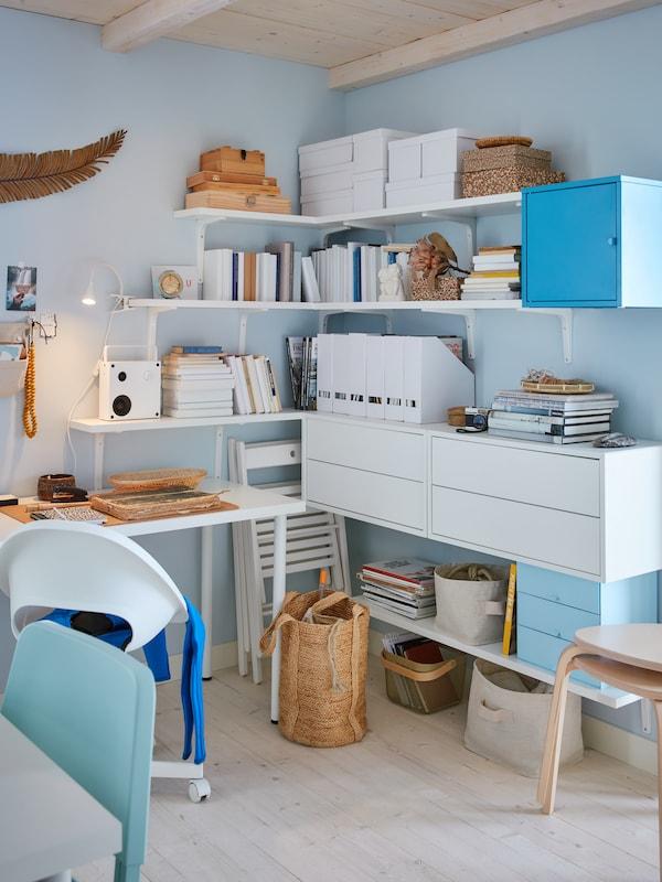 Białe półki, szafki z szufladami i szafka z drzwiami zamontowane na ścianie w rogu pokoju, obok biurka.