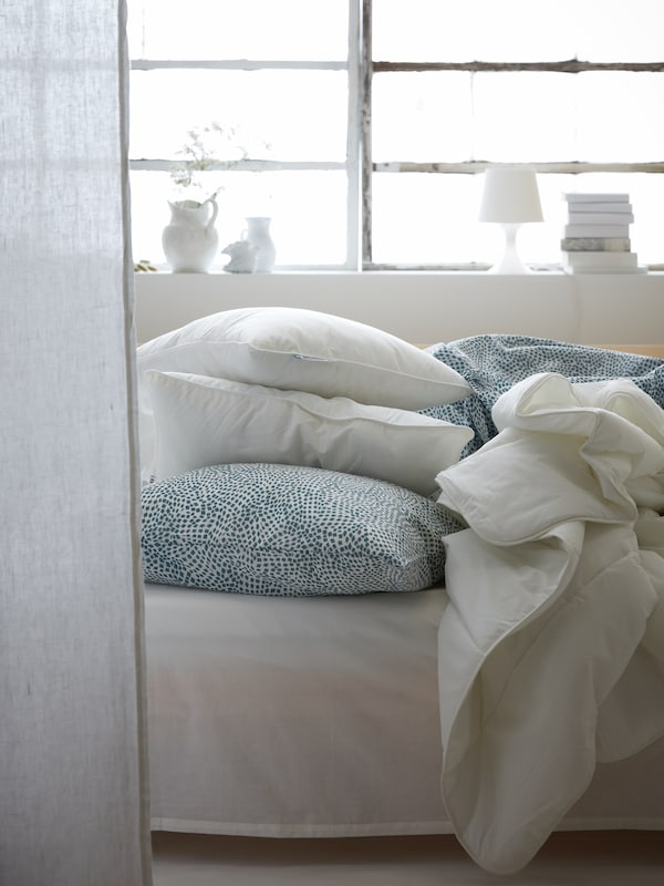In a bright, sunlit room, a SMÅSPORRE duvet, pillows and TRÄDKRASSULA bed linen lie in a heap on top of an unmade bed.