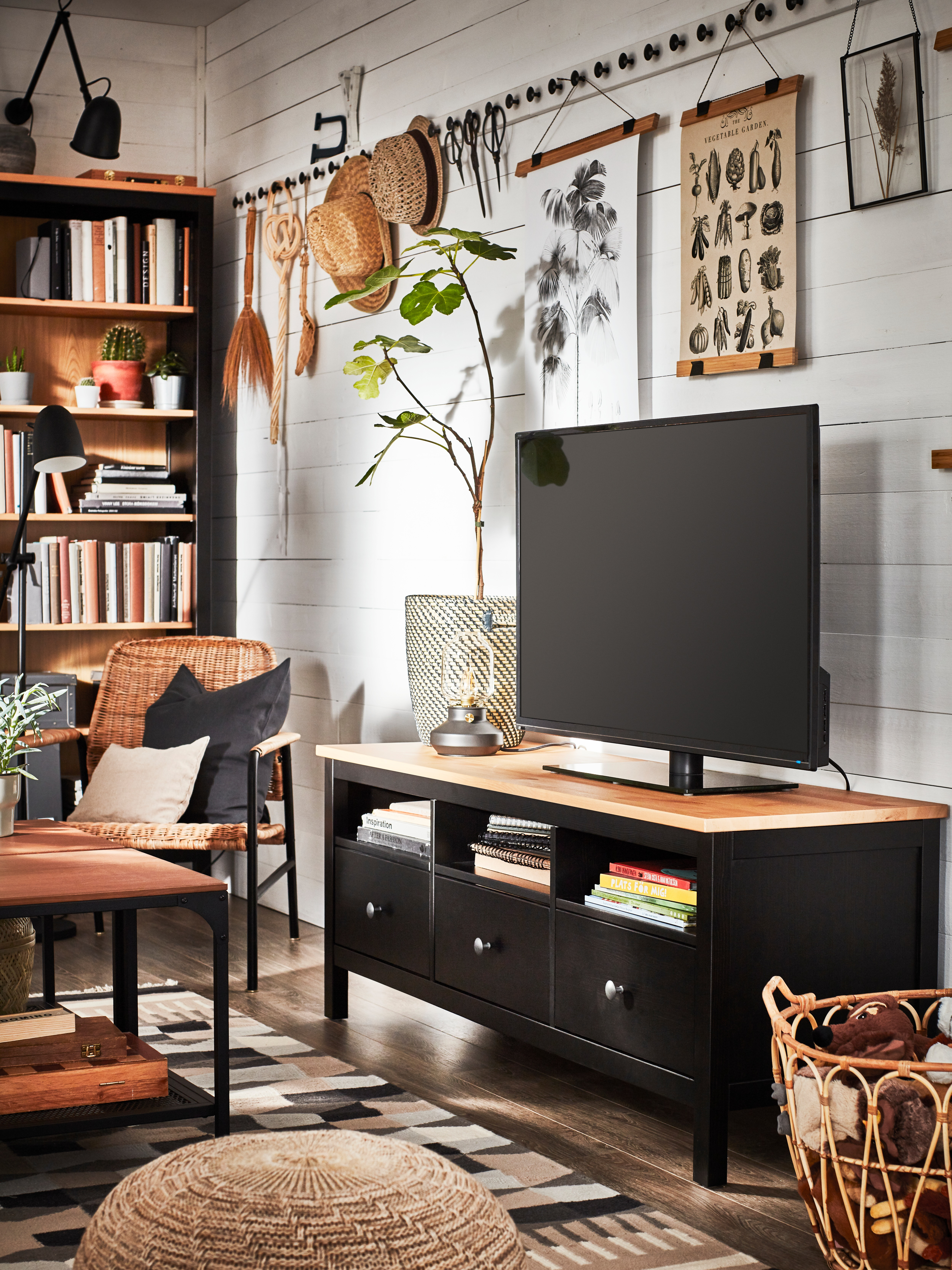 A black-brown/light brown HEMNES TV bench has a flatscreen TV on top, against a panelled wall with traditional decor.
