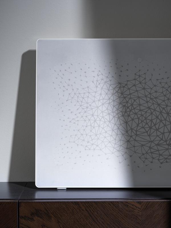 Gros plan du cadre avec enceinte WiFi SYMFONISK en blanc sur une étagère, partiellement à l'ombre.