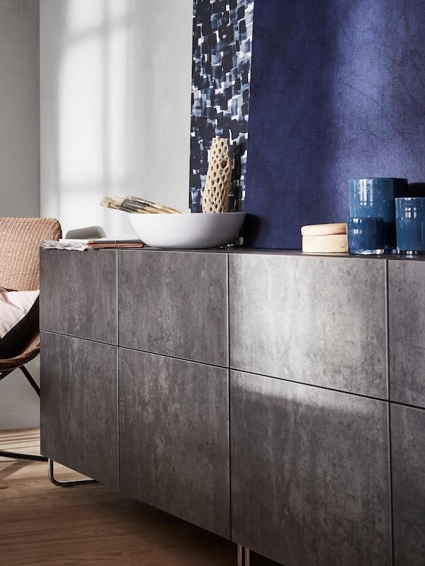 Die IKEA BESTÅ Aufbewahrungskombinationen mit Türen in dunkelgrauem Betonmuster sind hier mit gebogenen Metallfüßen versehen.