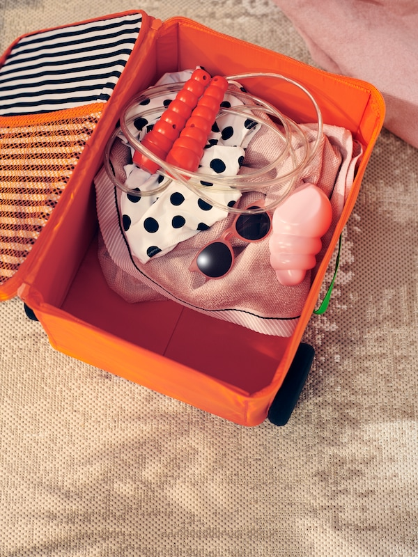 A skipping rope, sunglasses and other beach gear are packed into an orange storage box that looks like a rolling suitcase.