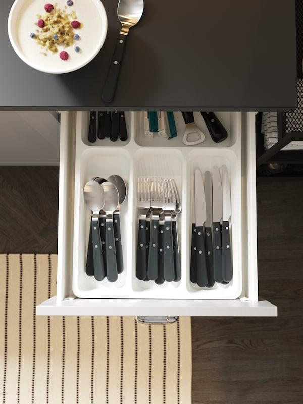 Otevřená kuchyňská zásuvka s příborníkem a úhledně uloženými příbory. Na podlaze je pruhovaný koberec.