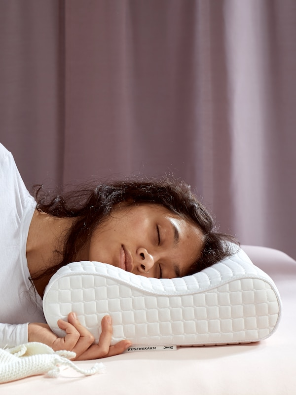A person wearing a white top asleep on a ROSENKÄRM pillow on white bed linen with a lilac curtain behind.