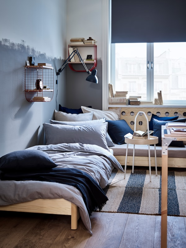 An UTÅKER stackable bed with both bed sections in use stands in a blue room. A dark grey TERTIAL work lamp is on the wall.