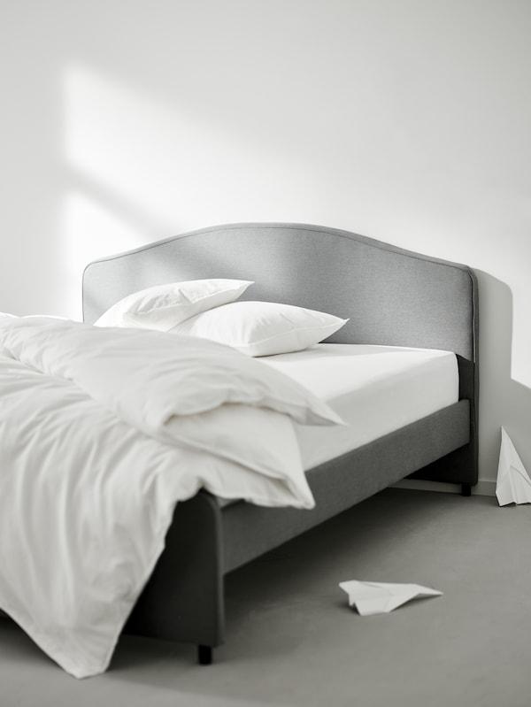 เตียงบุนวม HAUGA/เฮากา สีเทาพร้อมผ้านวมและหมอนสองใบและผ้าปูที่นอน ÄNGSLILJA/เอ็งส์ลิลยา เครื่องบินกระดาษสองลำวางอยู่บนพื้นใกล้ๆ