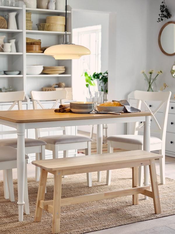 Miza v barvi hrasta in beli barvi, štirje beli stoli ter klop iz brezovega lesa stojijo na preprogi iz jute. V ozadju sta dve visoki omari.
