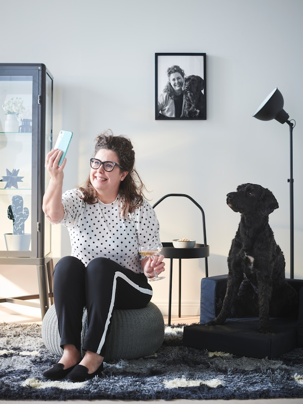 Woman sitting on pouffe, taking selfie with her large dog sitting on LURVIG sofa