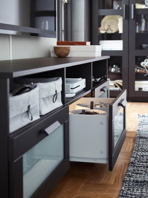Die IKEA BRIMNES TV-Bank mit offenen Fächern und integrierter Beleuchtung in den Schubladen.