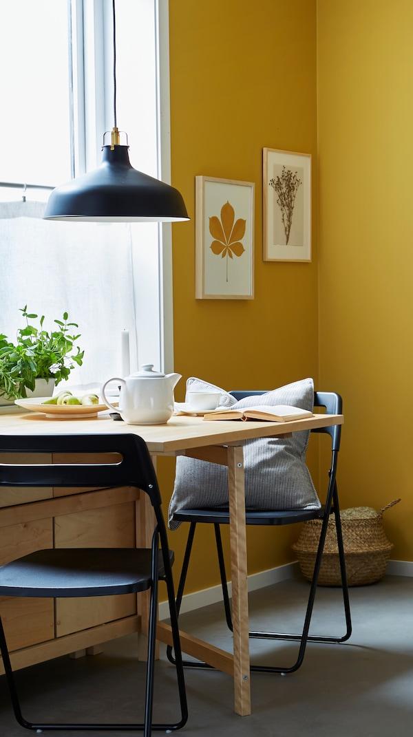 На жовтому килимі в орнамент стоїть стіл і шість стільців з берези; на столі на підставці стоять чайник і кухлі.