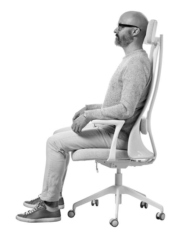 A bald man with black glasses and a beard sits in profile in a JÄRVFJÄLLET office chair.
